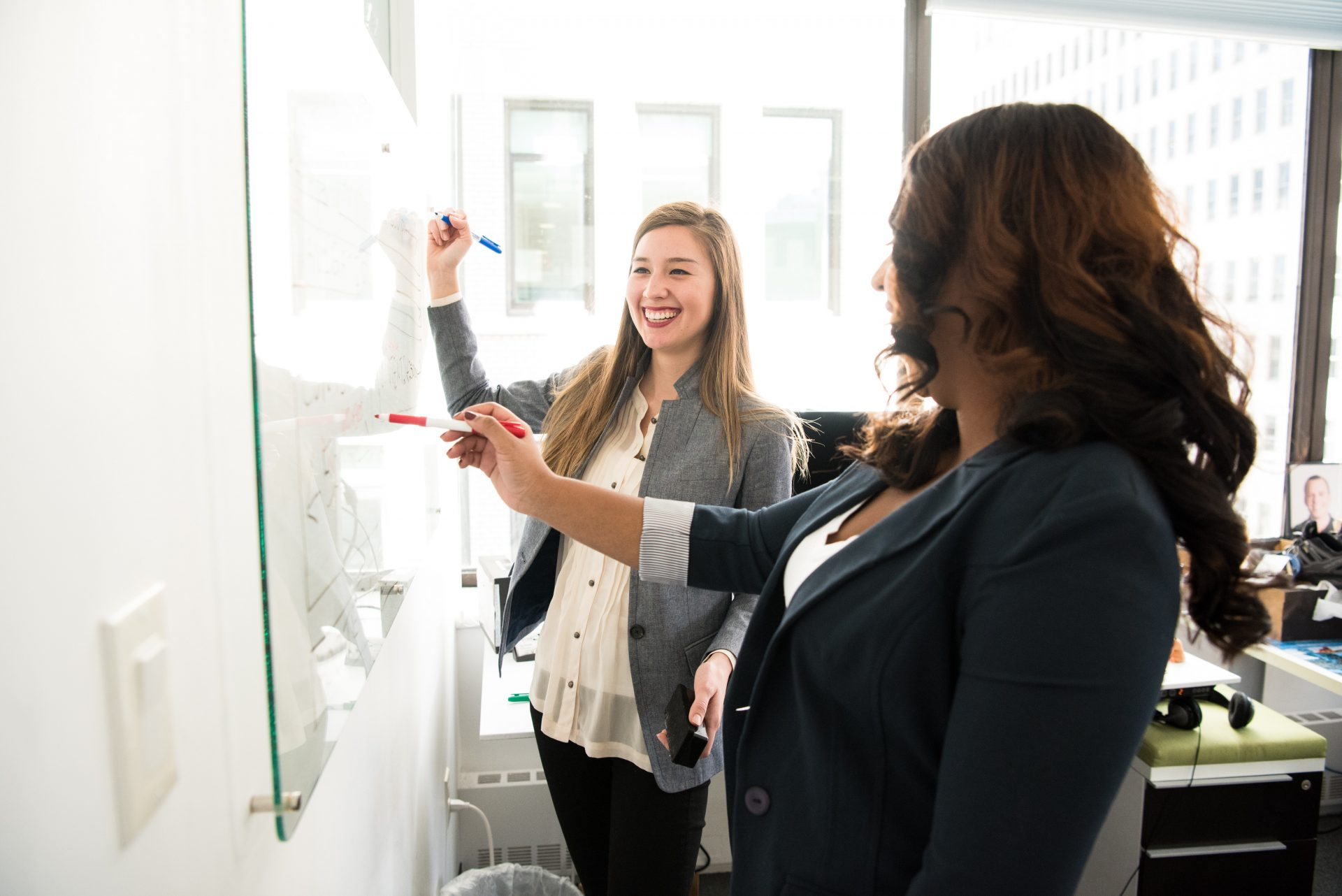 Two employees working at a dry erase board
