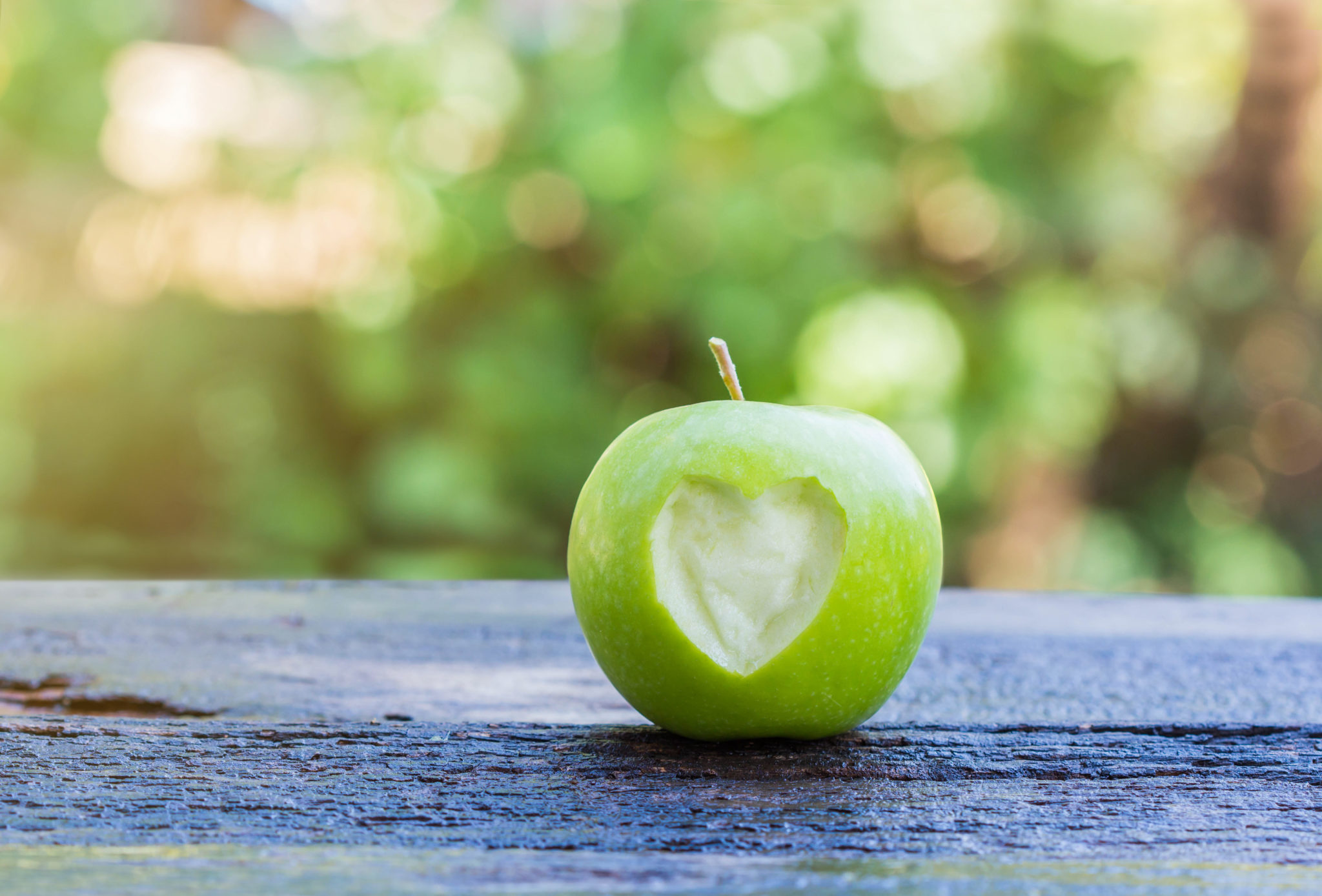 fresh green apple with heart shape cut out of it on wooden table.