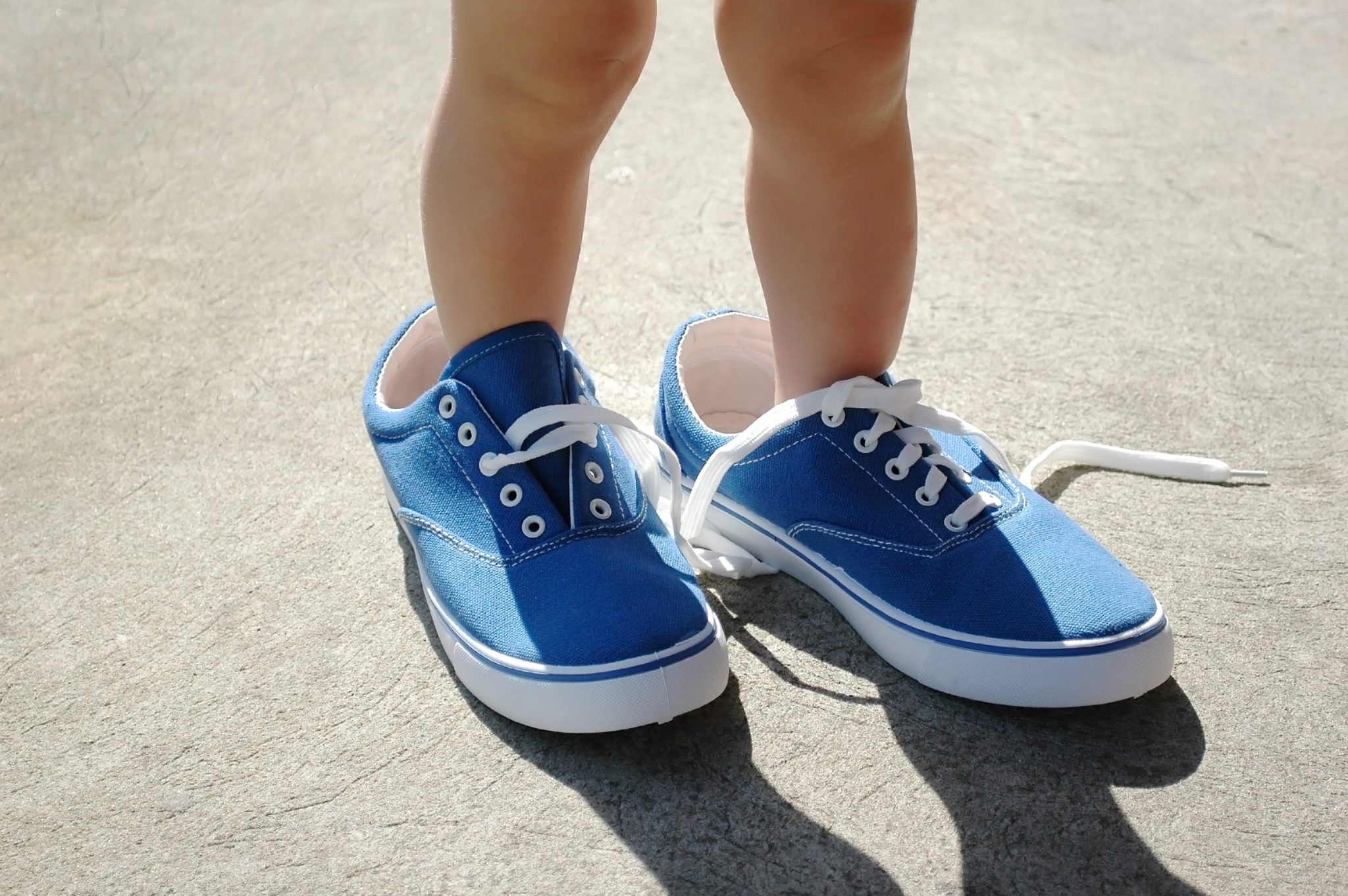 Baby foot stepping into adult size blue shoes