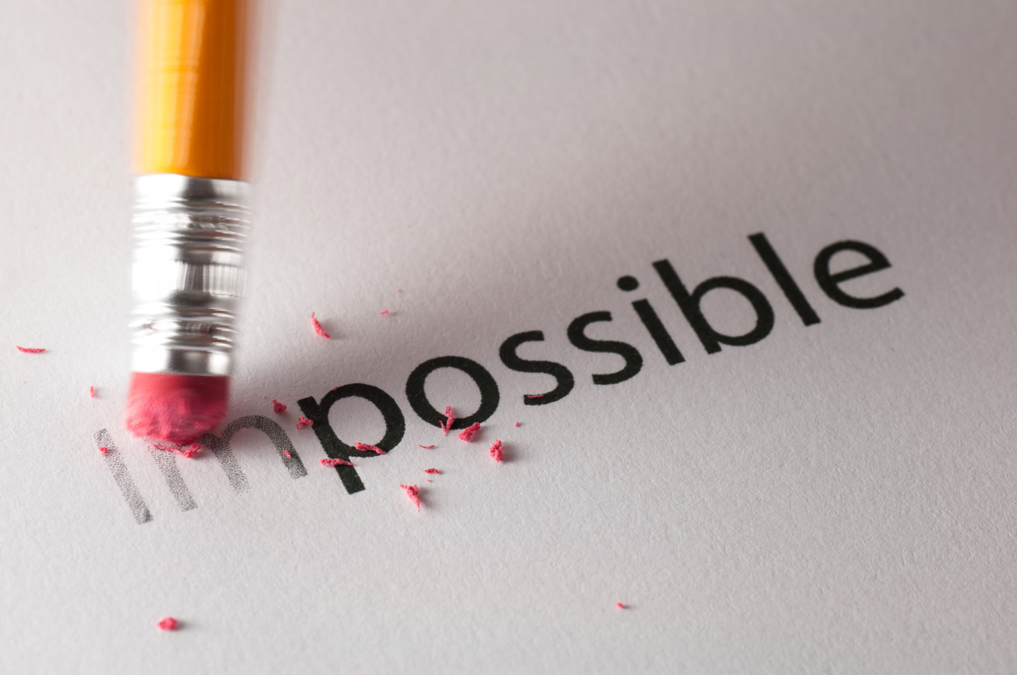 The word impossible with an eraser changing the word to possible