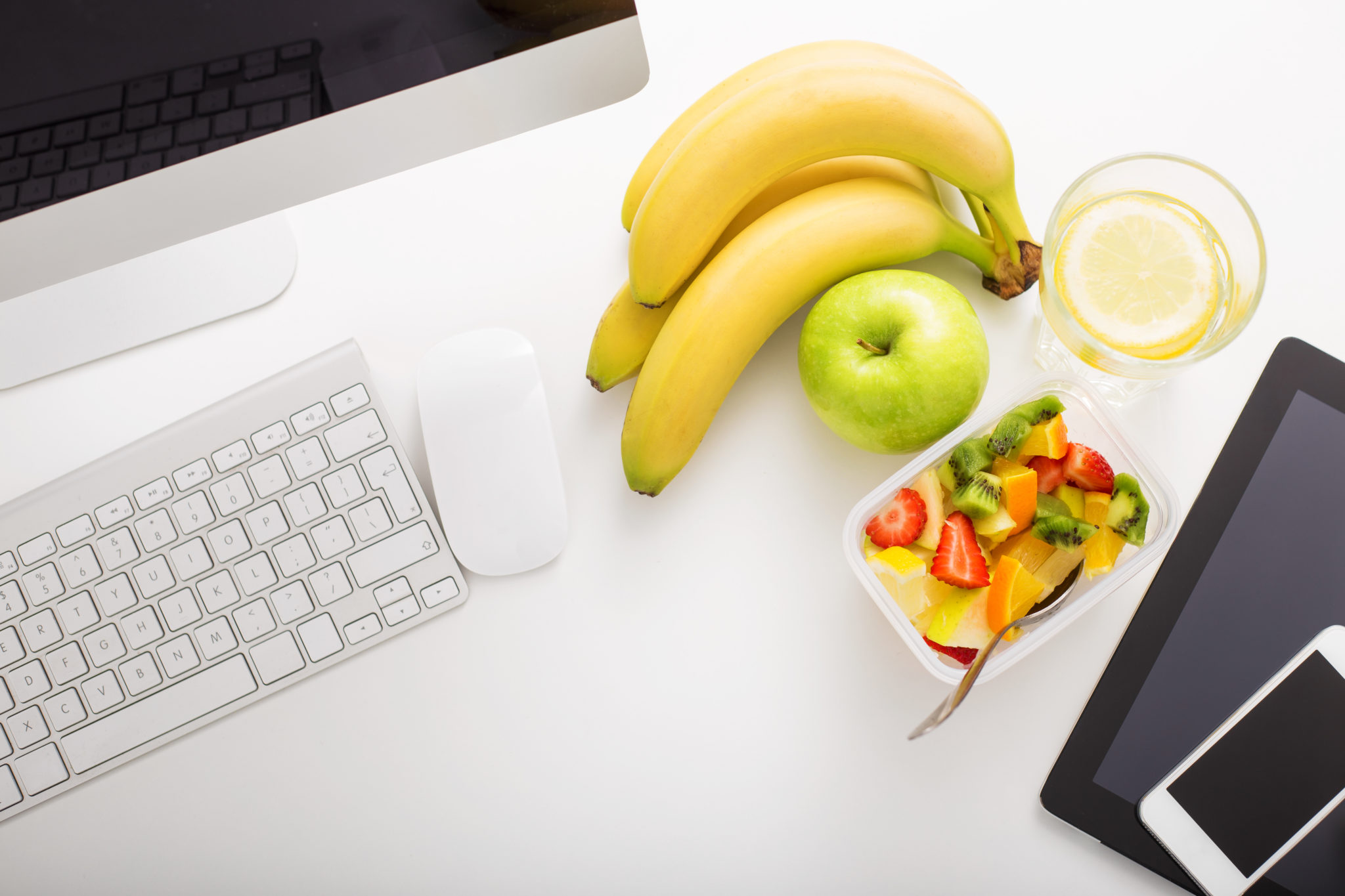 Close up of healthy food (banana, apple, fruit salad, and juice) on a work desk next to a desktop computer, tablet device, and cellphone