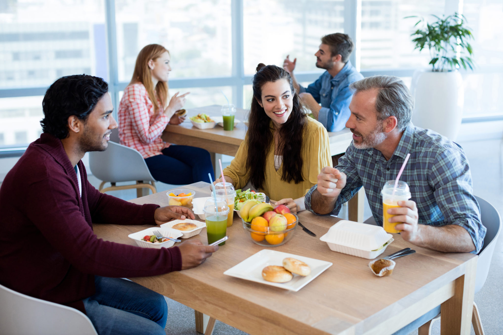 Better Employee Health for group of three coworkers eating a healthy lunch in a cafeteria