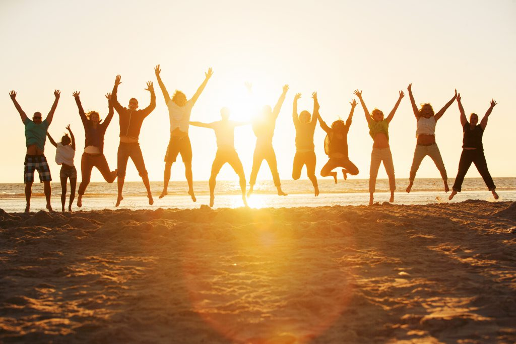 Twelve happy people jumping at the beach during a fantastic sunset