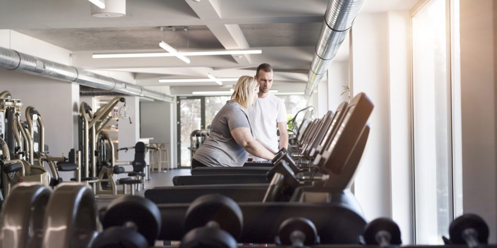Woman on treadmill in gym with a personal trainer beside her coaching her