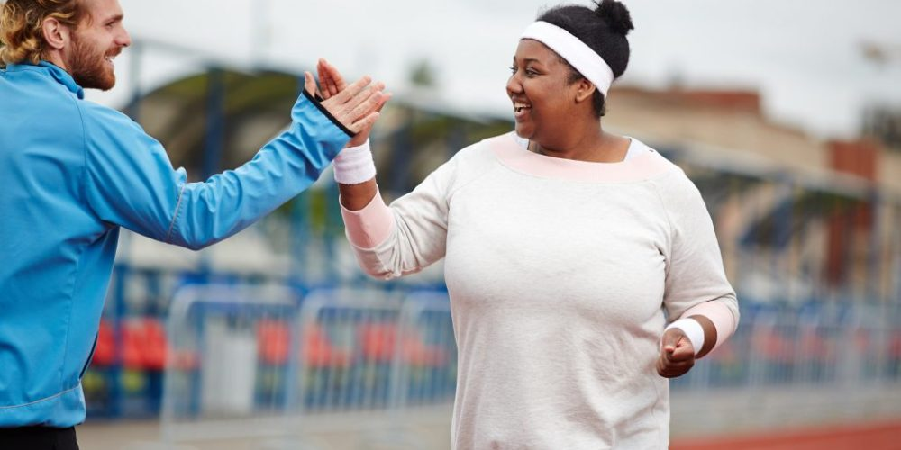 Happy plus size woman giving high five to her personal trainer while running on track on a path to making your new year's resolution stick