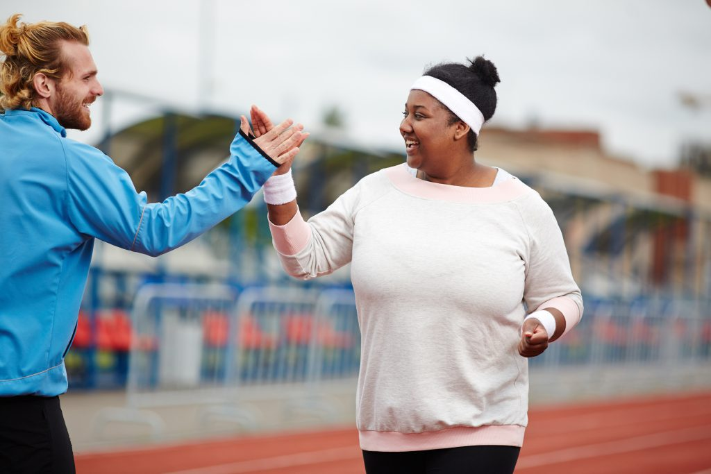 Happy plus size woman giving high five to her personal trainer while running on track