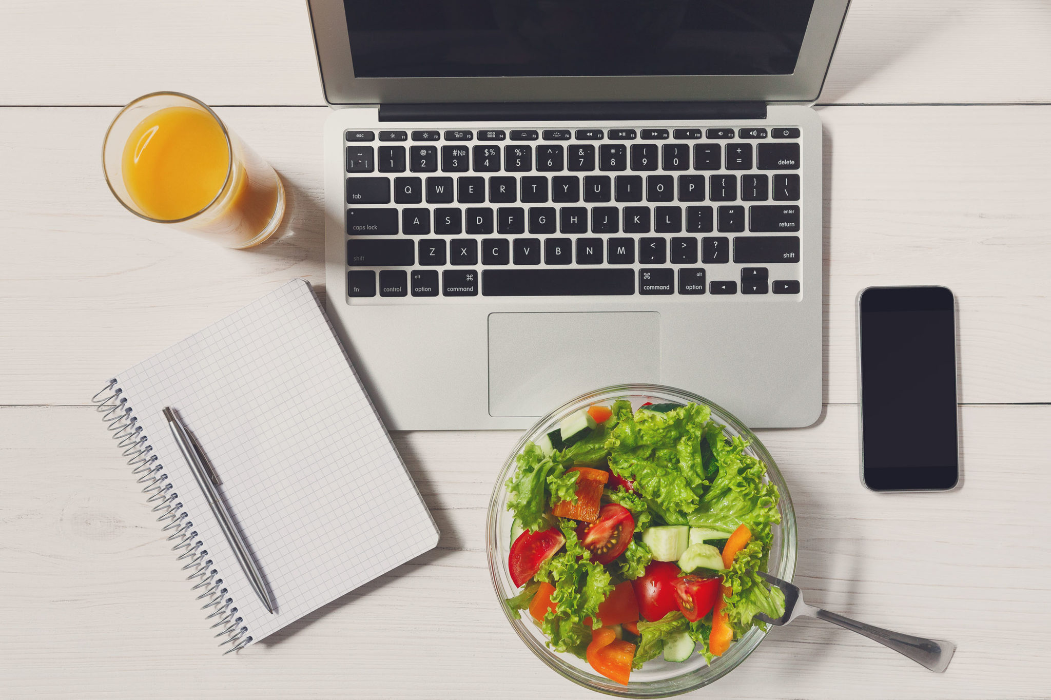Healthy salad and juice next to a laptop and productivity tools