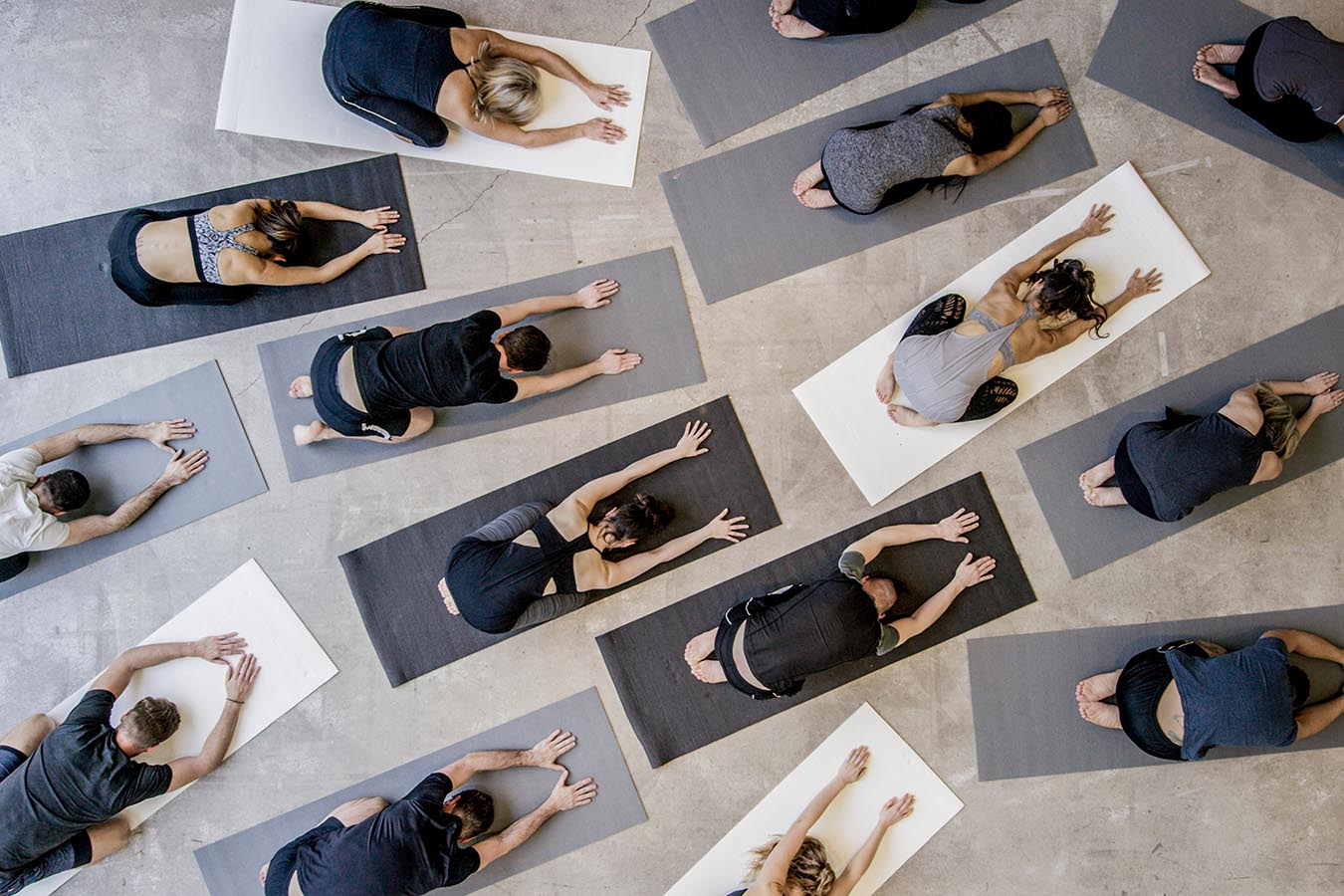 An aerial shot of a multi ethnic group of men and women practice yoga on on mats while wearing grey, black and white in an industrial setting. They are reaching forward in child's pose.