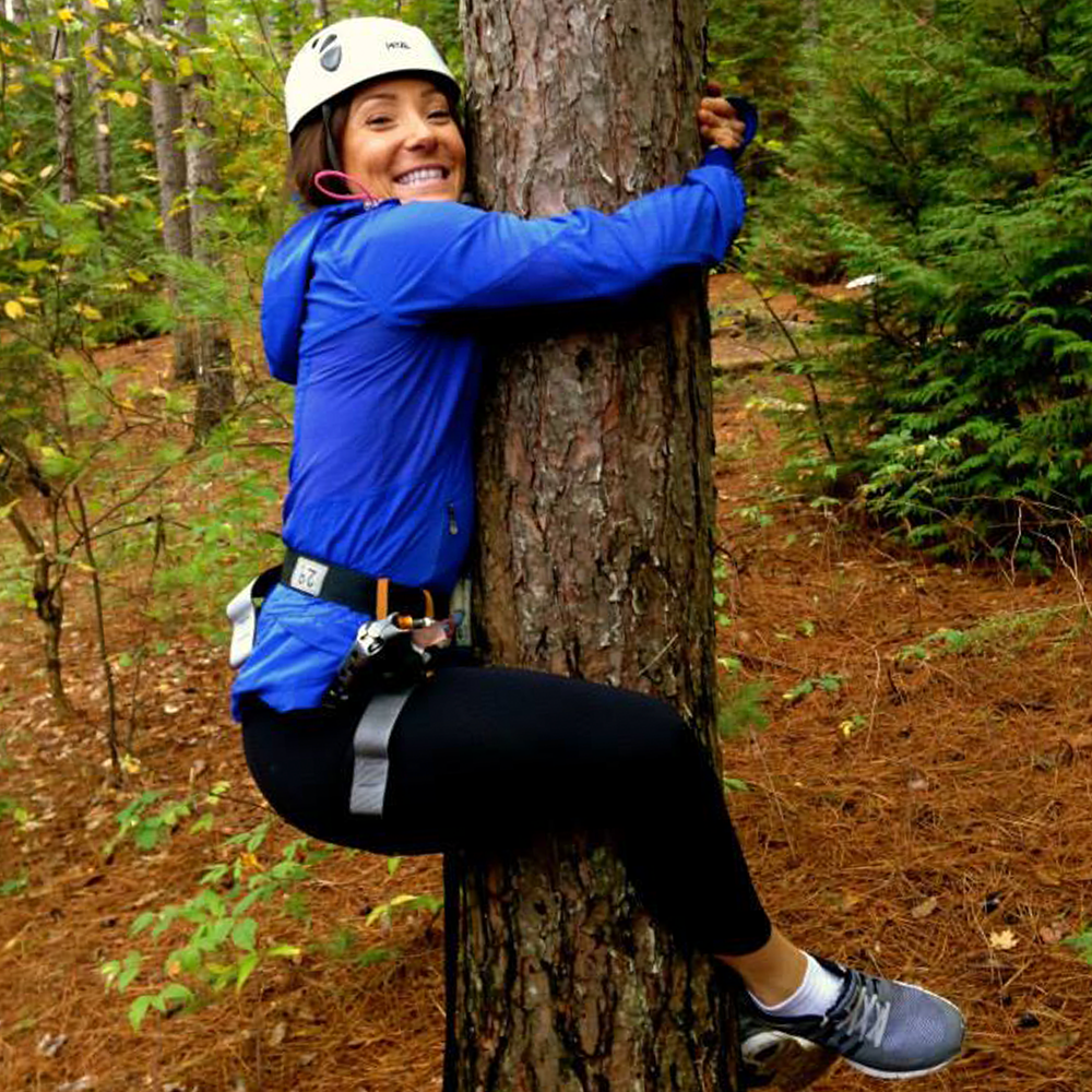 person smiling while hugging a tree outdoors