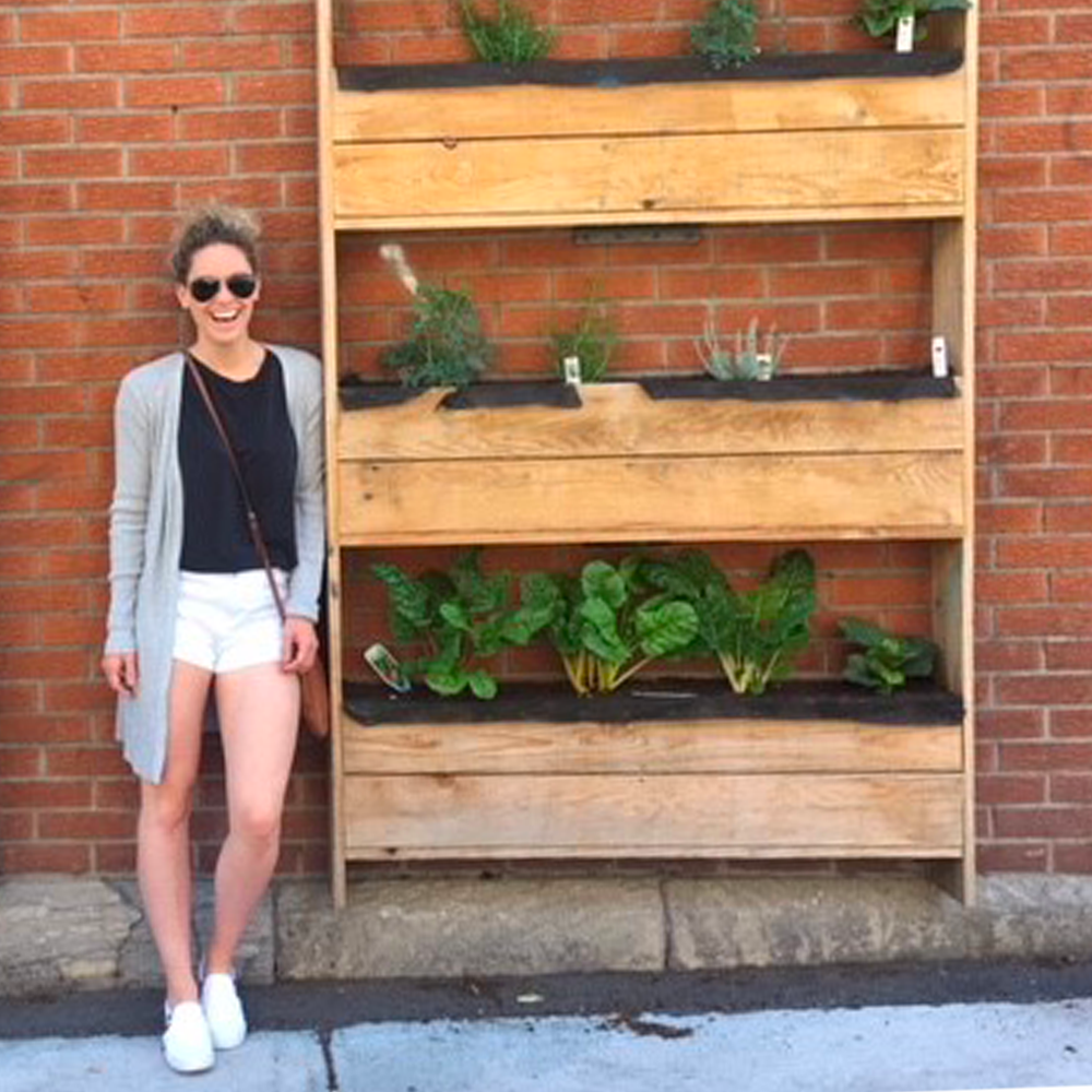 person smiling outdoors next to a vegetable garden