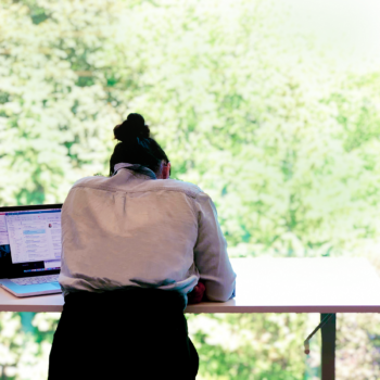 person working at a standing desk overlooking a park