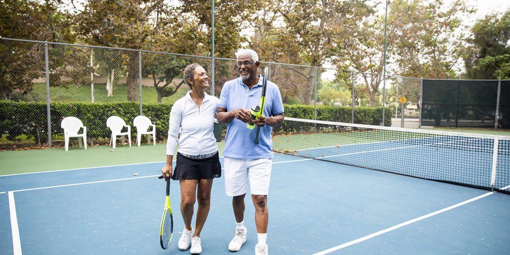 Elderly couple standing on a tennis court