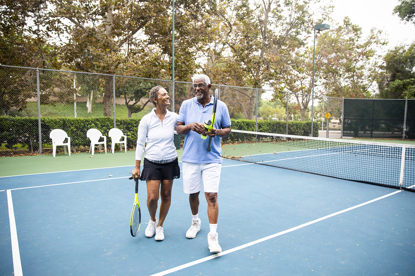Elderly couple standing on a tennis court