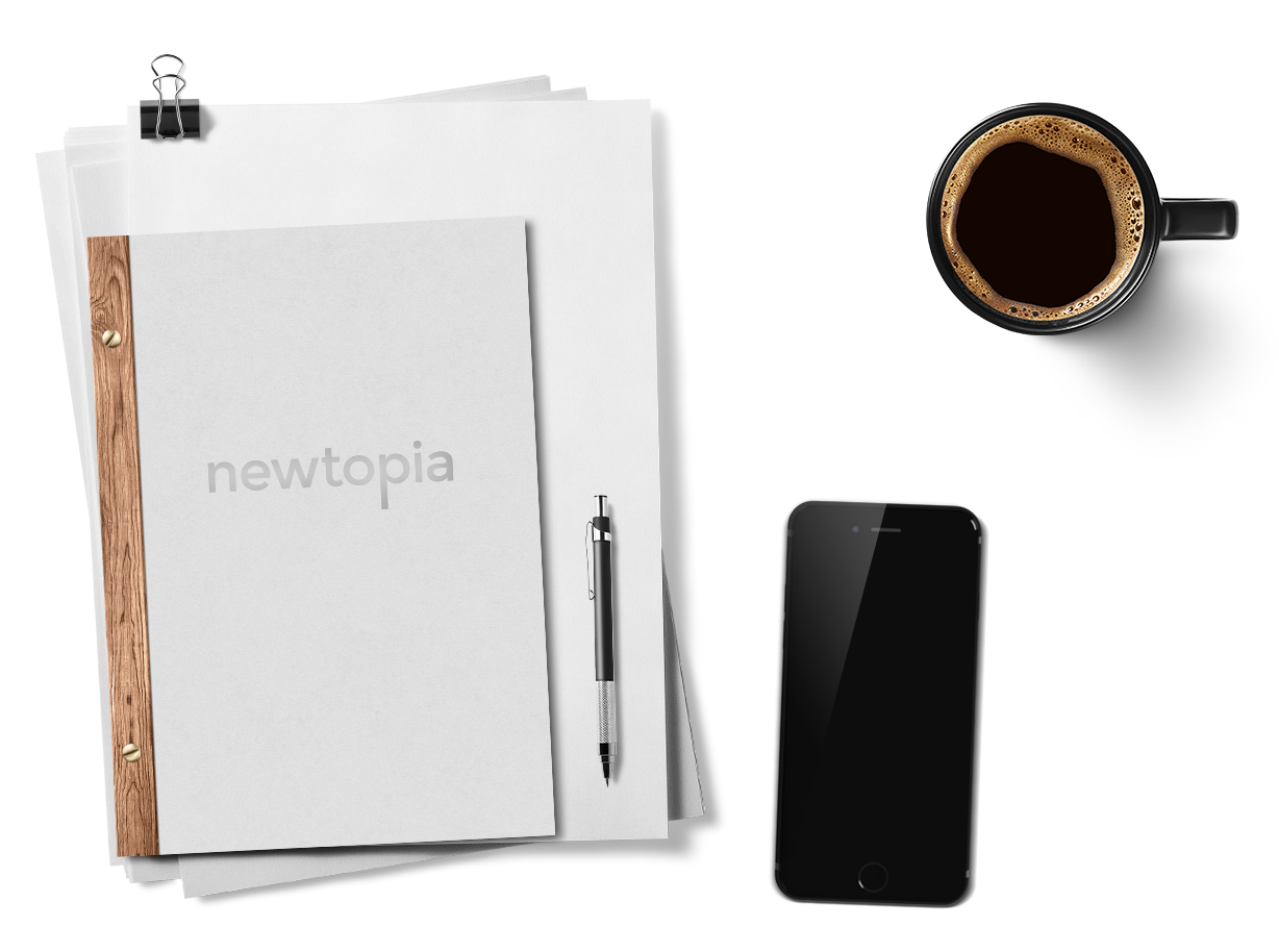 a Newtopia notebook next to an iPhone and a cup of coffee