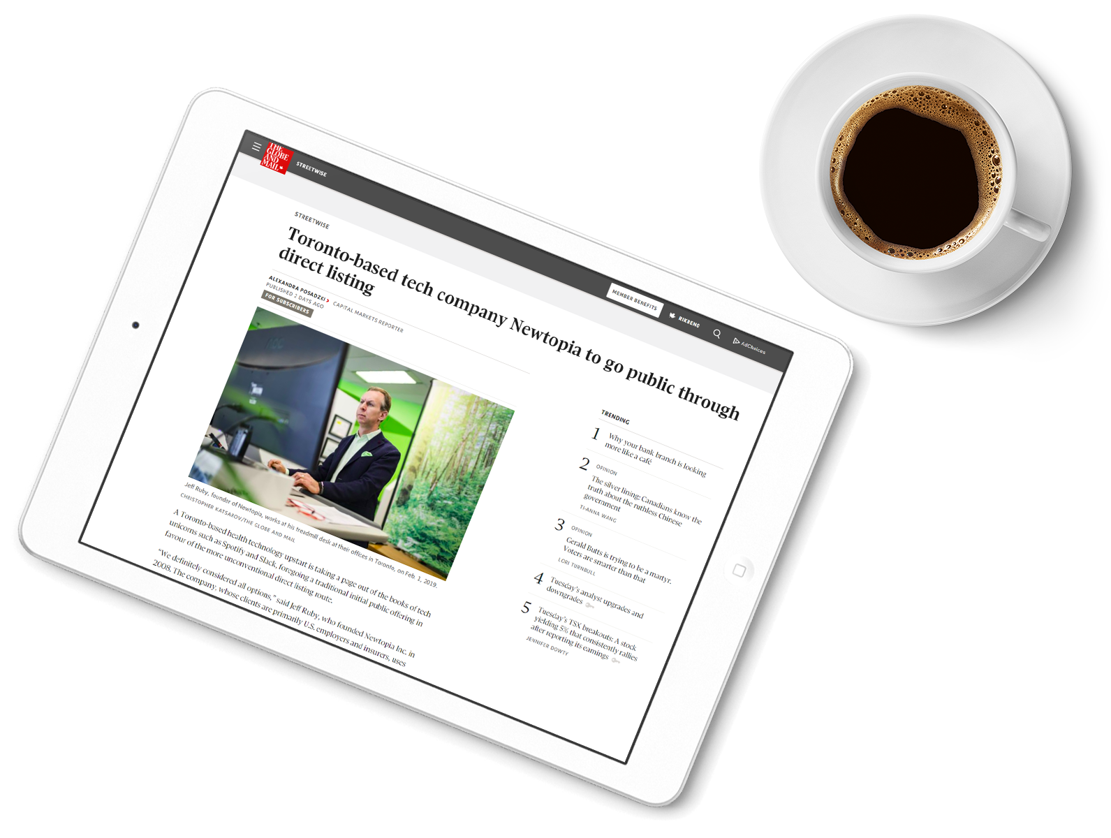An iPad showing a news article featuring Newtopia next to a cup of coffee
