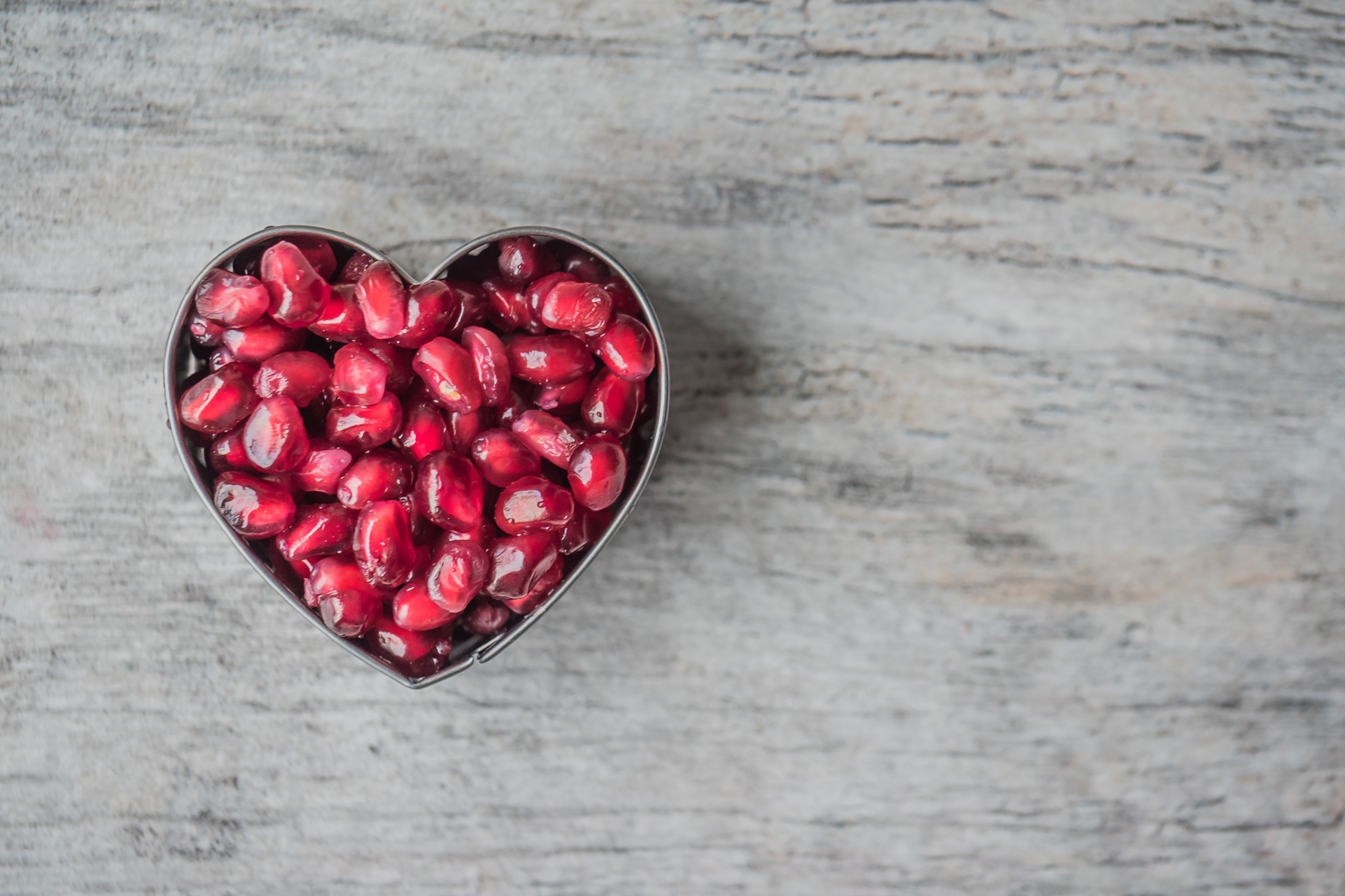 Heart shaped metal bowl filled with pomegranate seeds