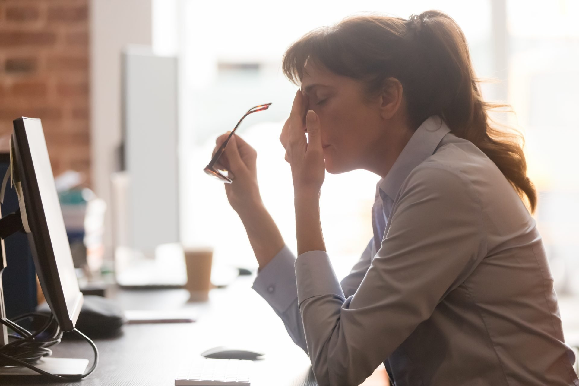Stressed Woman at computer screen with headache