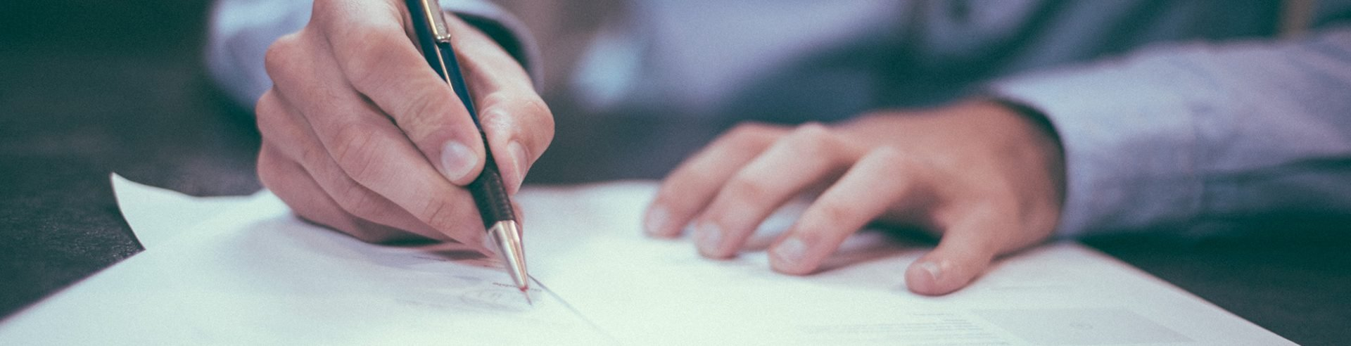 Image of man making notes with a pen