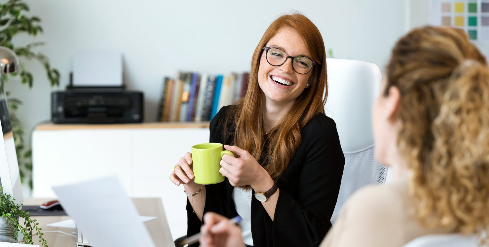 Woman laughing while chatting with a coworker. Woman is holding a green mug.