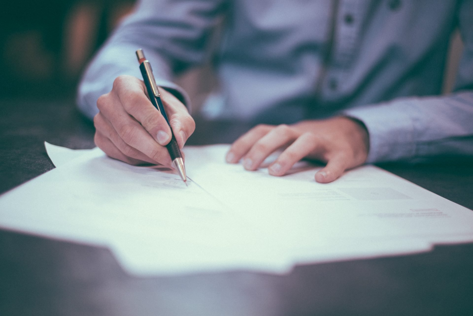 Person writing on a piece of a paper using a pen