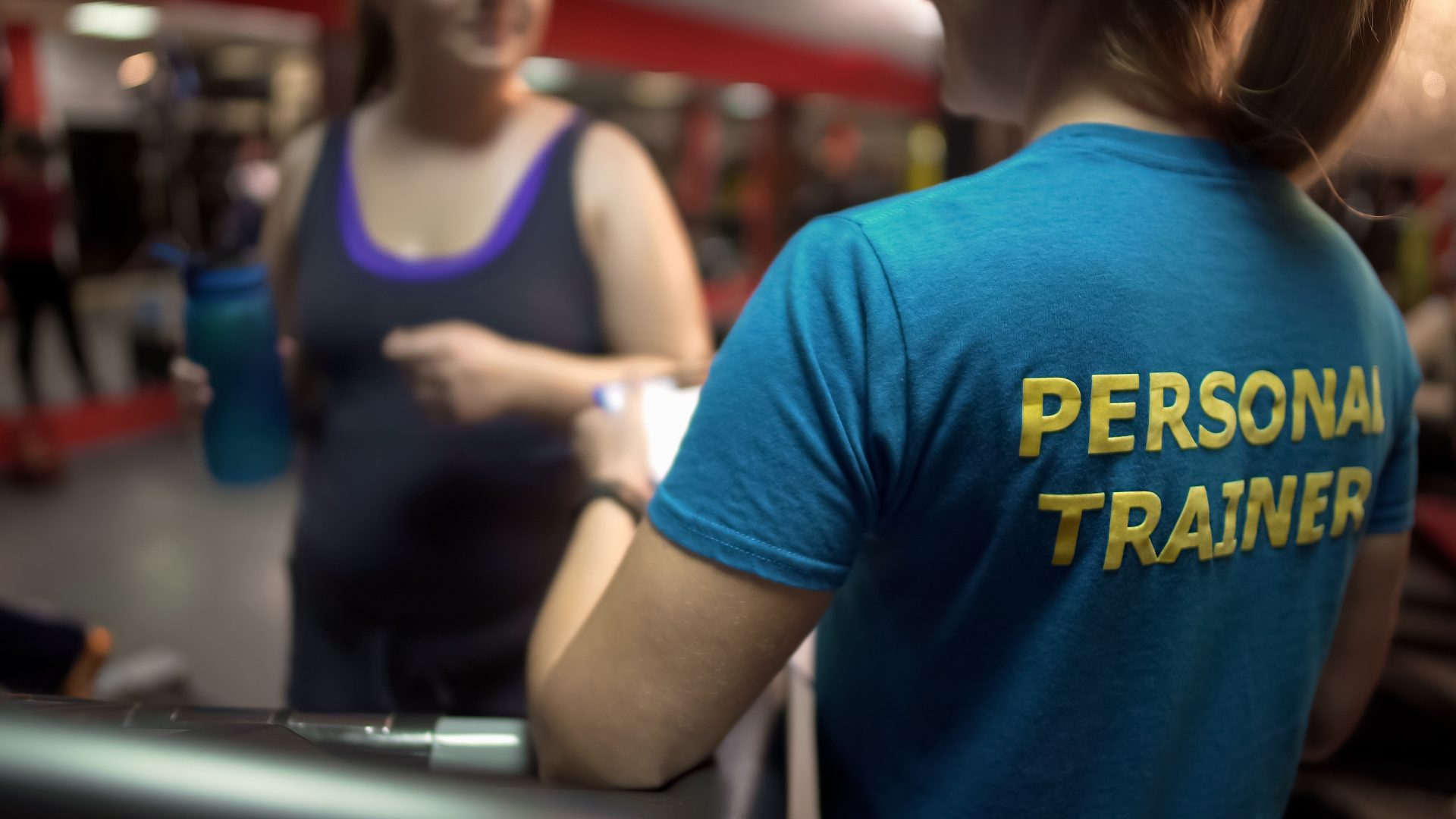 personal trainer working with client in a gym
