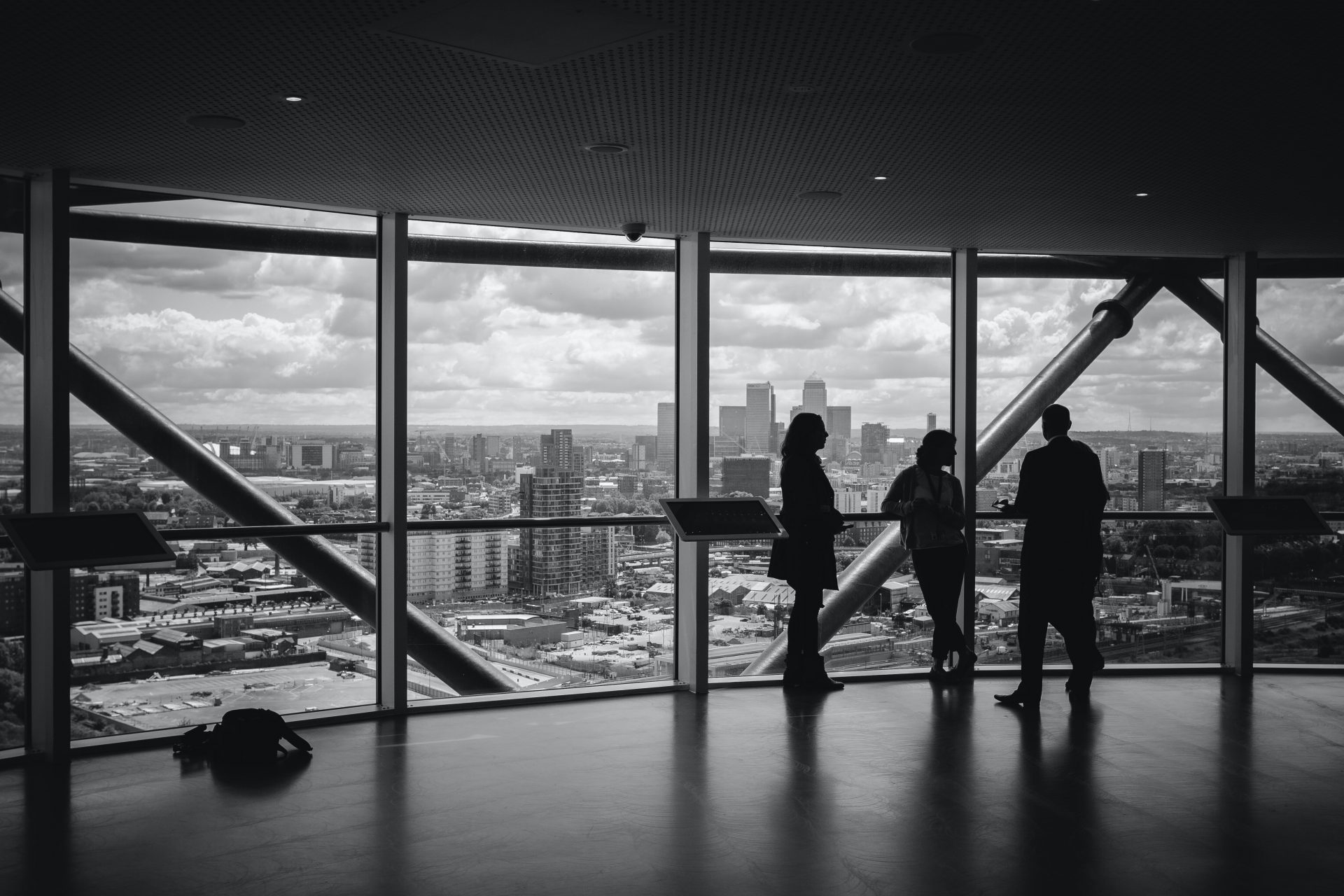 3 people looking at the city skyline out of floor to ceiling windows