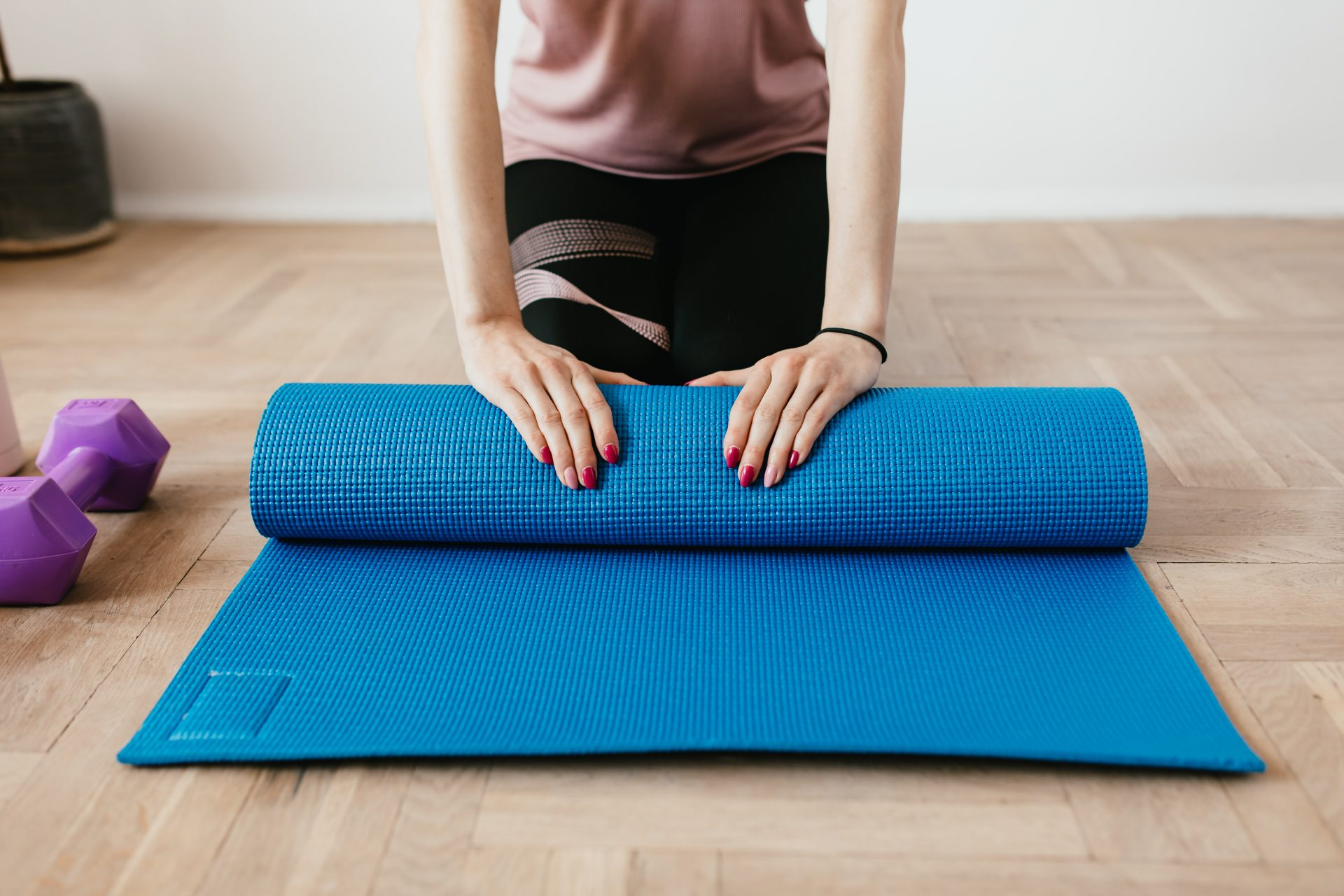 person rolling up a blue yoga mat with weights to the side
