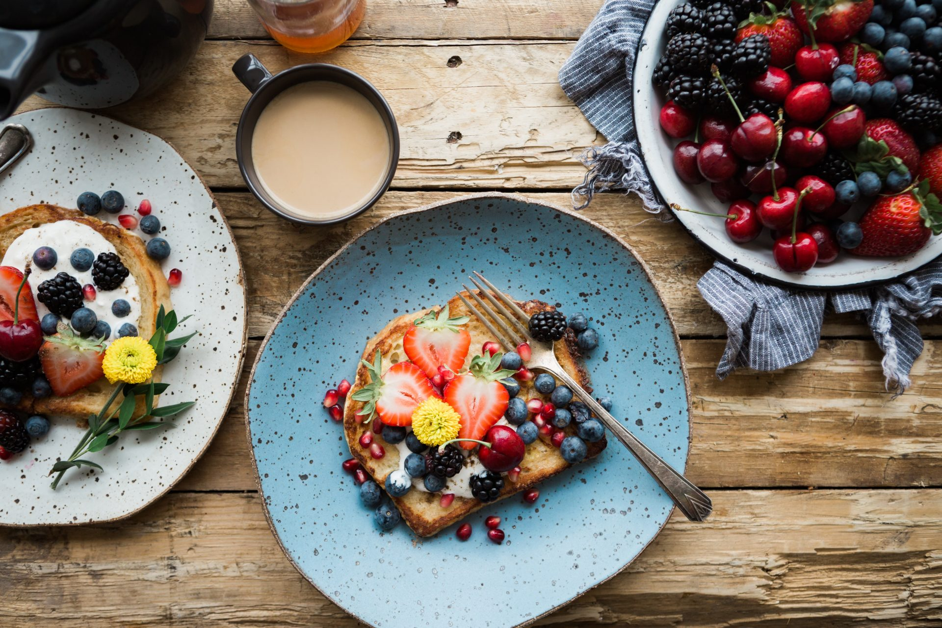piece of toast with fruit on it on a blue plate, with a cup of coffee and fruit to the side