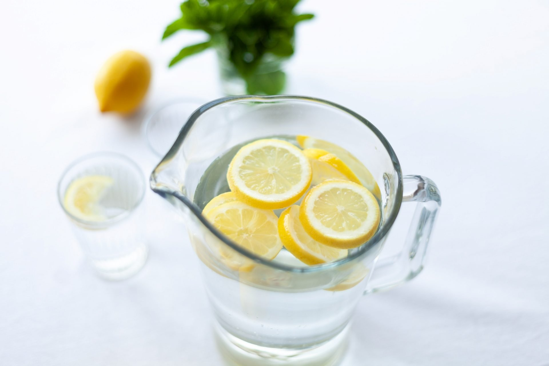 clear glass pitcher of lemon water