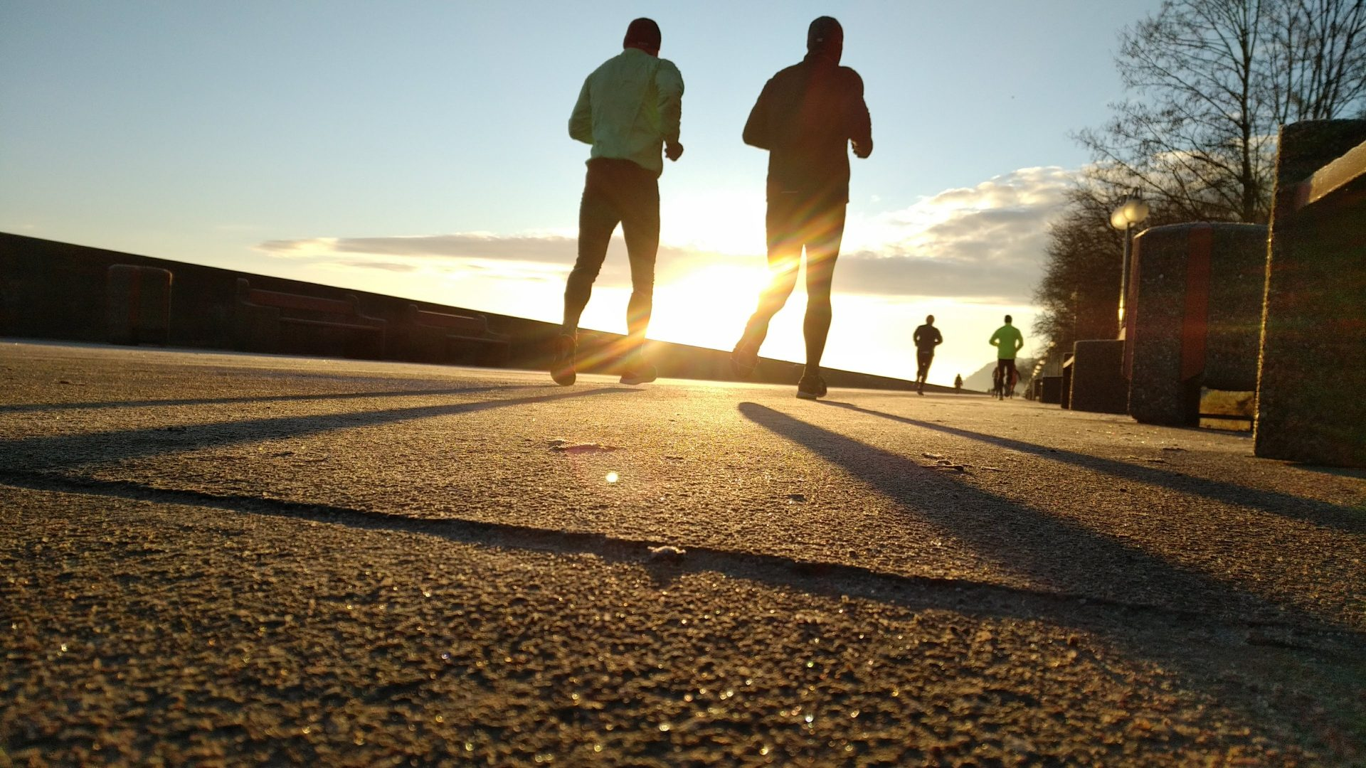 two people running on the road during sunset